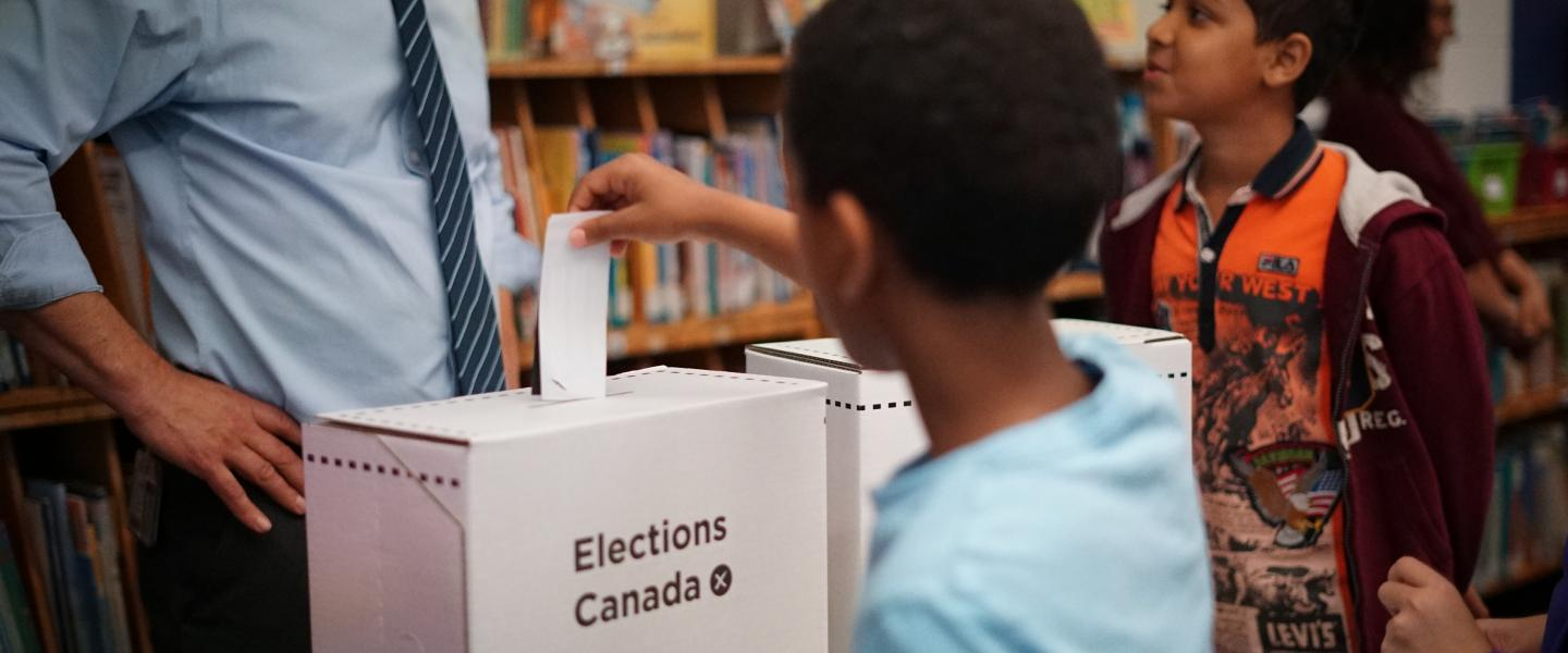 Student inserting a ballot in ballot box