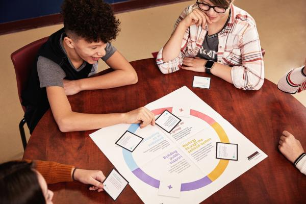 Students at a round table placing cards on an activity board. - A une table ronde, des élèves placent des cartes sur une planche de jeu.