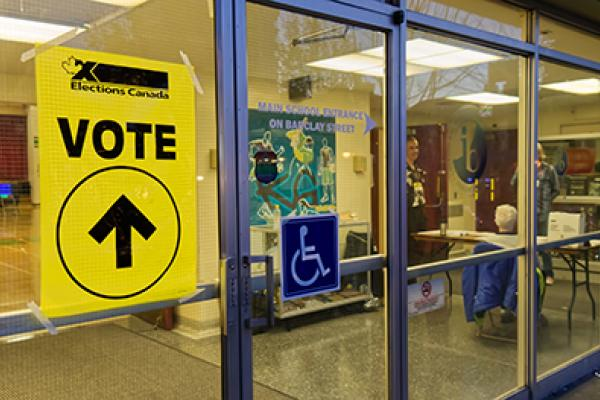 "Windows and front door of a polling station. On a window, a yellow poster reads: ""vote"". Inside the building there is a registration table. The door features a wheelchair symbol. - Fenêtres et porte d'entrée d'un bureau de vote. Sur une vitrine, une affiche jaune lit: ""vote"". À l'intérieur du bâtiment il y a une table d'enregistrement. Une affiche d'un fauteuil roulant est accrochée à la porte."