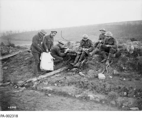 Black and white photograph of a group of soldiers in an empty battlefield marking their ballots.