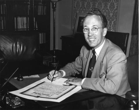 Black and white photograph of Tommy Douglas sitting in his office, signing and official document and smiling at the camera.