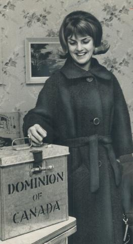 Black and white photograph of a young women placing her ballot in a metal ballot box, while smiling.