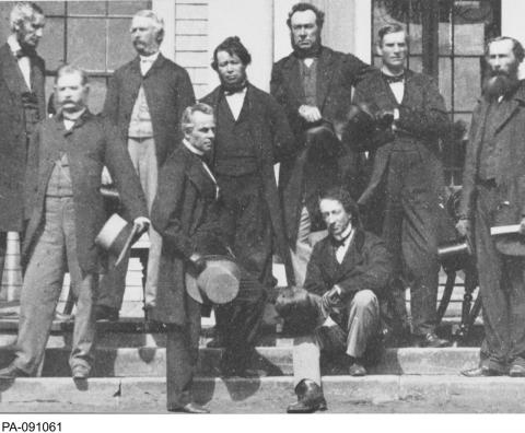 Black and white photograph showing a group of men, including Sir John A. MacDonald, gathered on steps holding their top hats.