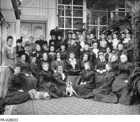 Black and white photograph showing a large group of women, positioned in rows. Two dogs sit in front.