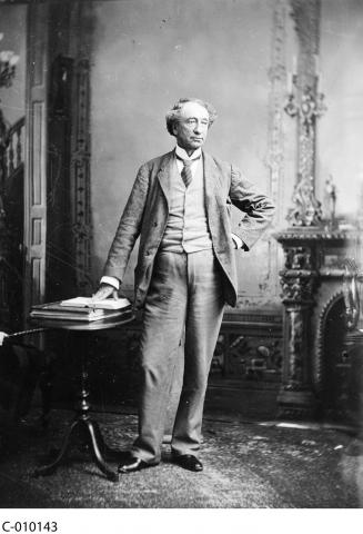 Black and white photograph of Sir John A. MacDonald standing in front of a fireplace, one hand on his hip, the other touching an open book on a small table beside him.