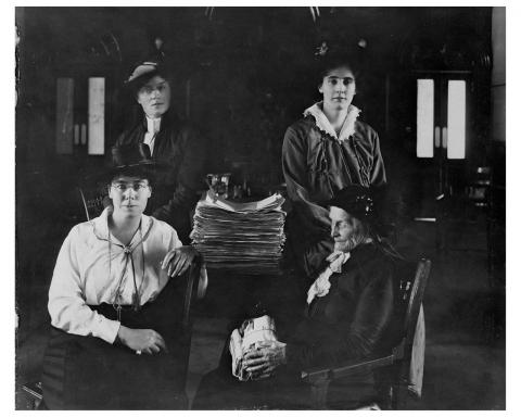 Black and white photograph showing four women seated around a table. On the table is a large stack of paper.