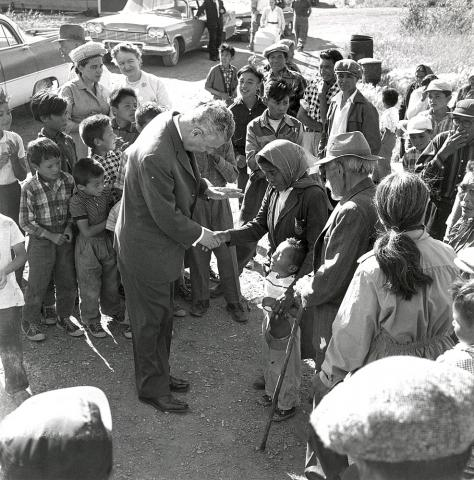 Black and white photograph showing Prime Minister John Diefenbaker shaking hands with a First Nations woman, amid a small crowd of people of all ages. The woman has her arm around a young child.
