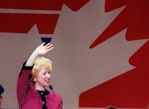 Photograph of Kim Campbell standing behind a microphone, smiling and waving.