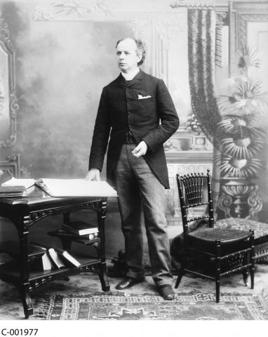 Black and white photograph of Wilfred Laurier, standing beside a table with his hand resting on a large open book.