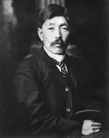 Black and white photograph of a mustachioed Japanese man, taken from the waist-up, holding his hat in his hands.