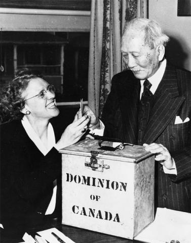 "Photograph of an elderly Japanese man holding a ballot next to a seated smiling women. They are pictured behind a metal ballot box that reads: ""Dominion of Canada."""
