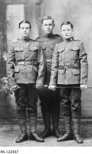 Black and white photograph of three young soldiers in uniform.