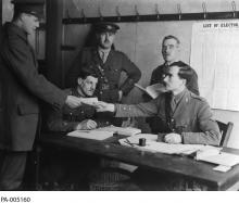 "Black and white photograph of a group of men wearing military uniforms, gathered around a table. One man gives a ballot to another man. On the wall is posted a paper that reads: ""List of Electors."""