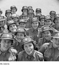 Black and white photograph showing a large group of women wearing military uniforms smiling at the camera.
