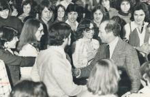 Black and white photograph of Prime Minister Pierre Trudeau shaking hands with a young person, while standing at the centre of a large group of smiling youth.