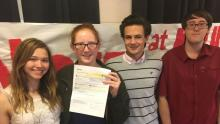 Photograph of four smiling teenagers holding up a piece of paper.