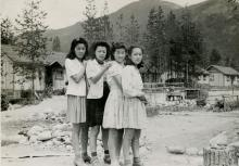 Black and white photograph of four young Japanese women standing in front of an internment camp, with their hands on one another's shoulders. Mountains are in the background.