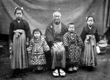 A black and white photograph of a Japanese family of five posing in traditional attire. An older gentleman sits in the middle, with two children on either side.