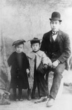 A black and white photograph of a Japanese man seated beside his two young children.