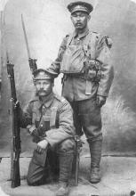 Black and white photograph of two Japanese men in military uniform, holding rifles at their sides. One man stands, and the other kneels on one knee in front of him.