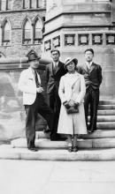 A black and white photograph of a group of four Japanese men and women, standing on the steps of Parliament.