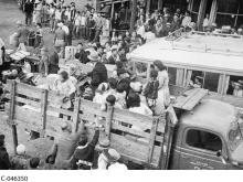 A black and white photograph showing many people of all ages being loaded into the back of a truck, with their luggage. Many others wait in line behind a rope barrier.