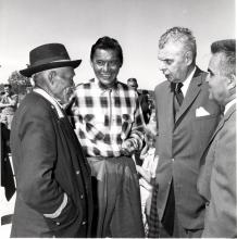 Black and white photo of John Diefenbaker with Chief Jimmy Bruneau of Rae, Chief Joe Sangris, and the Mayor of Yellowknife, Northwest Territories, in discussion.