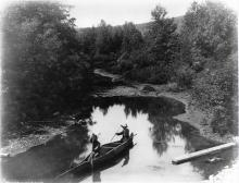 Black and white photo of two Indigenous men in a bark canoe in Restigouche, Quebec.]Black and white photo of two Indigenous men in a bark canoe in Restigouche, Quebec.