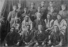 Black and white photo of the first time Indigenous men joined the Canadian Forces as soldiers.  First two rows: Indigenous men, some in traditional regalia. Last two rows: men in their soldier uniform.