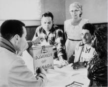 Black and white photo in Hiawatha Council Hall on the occasion of a federal by-election. The first votes cast since the right to vote was extended to all status Indians were those of the Rice Lake Band near Peterborough, Ontario. From left to right: Lawrence Salleby; Chief Ralph Loucks, Deputy Returning Officer; Lucy Muskrat, Poll Clerk; Eldon Muskrat, Poll Constable.